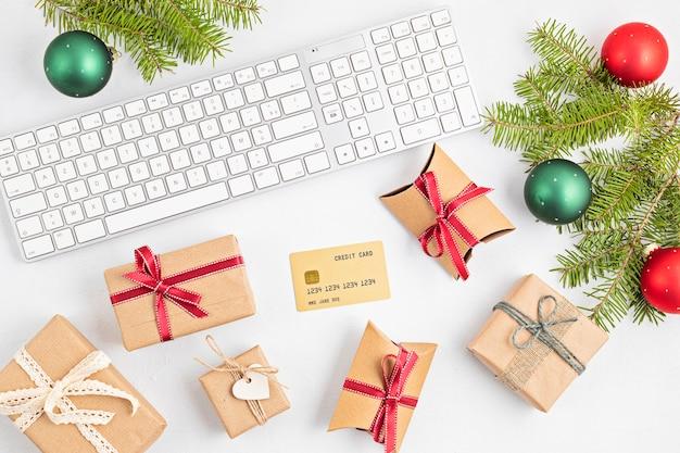 Online kerstwinkelconcept met geschenkdozen, toetsenbord en gouden creditcard. bovenaanzicht, plat gelegd