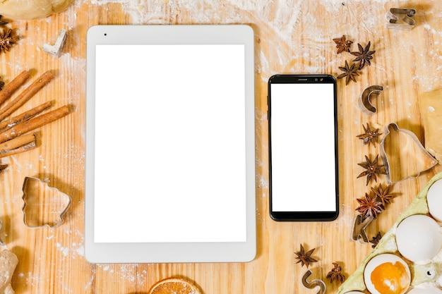 Online kookles. plat leggen van tablet en smartphone met witte schermen. houten tafel met bloem en gebakje ingrediënten.