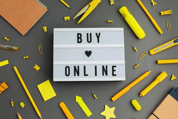 Online kopen. geel briefpapier schrijfgereedschap accessoires pennen potloden op grijze achtergrond. terug naar school. kantoorbenodigdheden producten