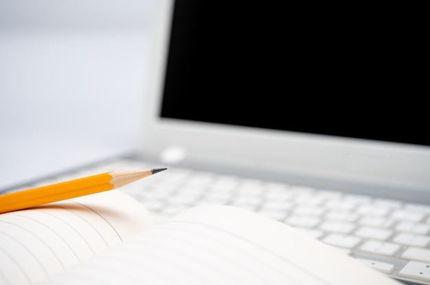 Online leerconcept. er is een gelinieerd notitieboek en een geel potlood op het toetsenbord van de laptop.