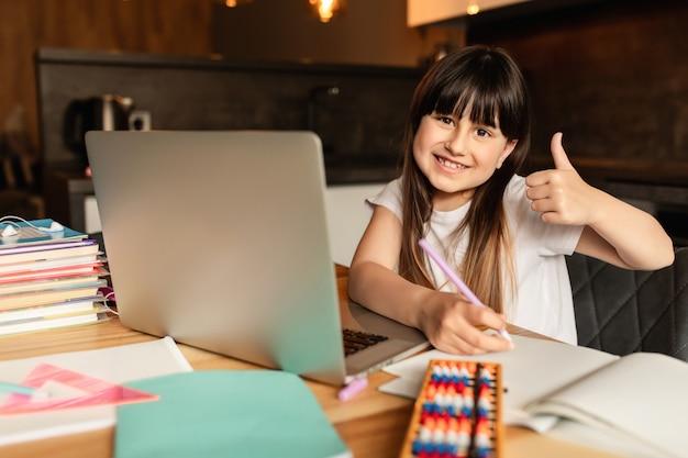 Online leren. gelukkig meisje dat thuis bestudeert. onderwijs en afstandsonderwijs.
