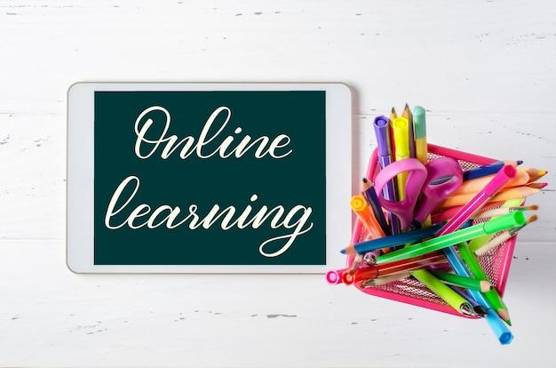 Online leren - handgeschreven inscriptie op een tablet. het concept van afstandsonderwijs voor kinderen. tablet- en kantoorbenodigdheden op een witte houten achtergrond.