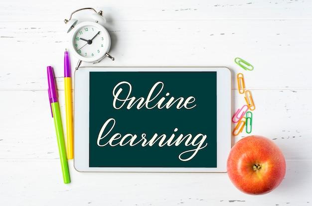 Online leren - handgeschreven inscriptie op een tablet. tablet- en kantoorbenodigdheden op een witte houten achtergrond.