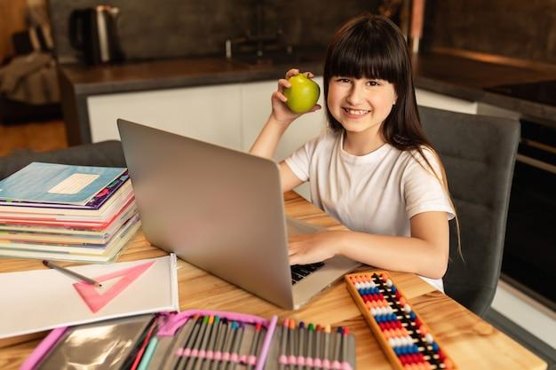 Online leren. het schoolmeisje met groene appel doet thuiswerk