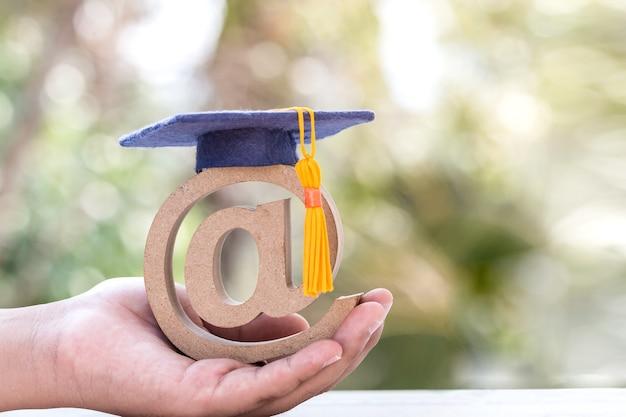 Online leren in het buitenland universitair onderwijsconcept: afstudeerpet op e-mailadressymbool in studentenhanden. ideeën communicatie internationale school, kan cursus leren door internettechnologie