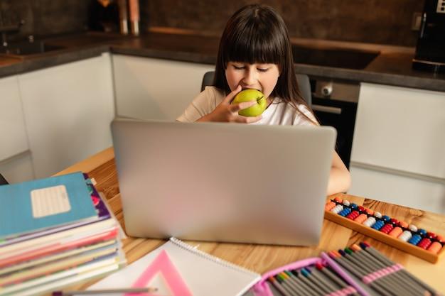 Online leren is goed voor de gezondheid. het schoolmeisje maakt huiswerk en eet thuis groene appel