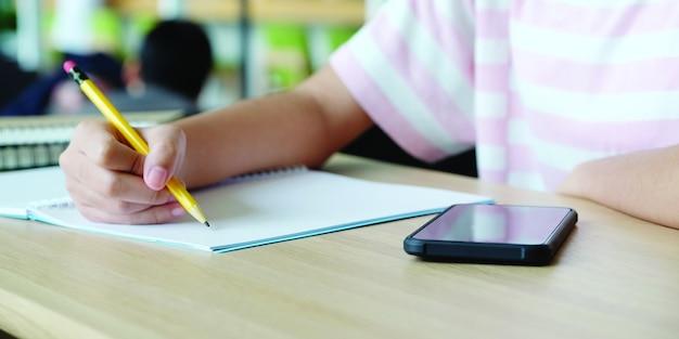 Online leren thuis school concept, close-up van college student hand schrijven notebook en smartphone op tafel, college onderwijs en communicatie op de campus, home school online onderwijs, e leren