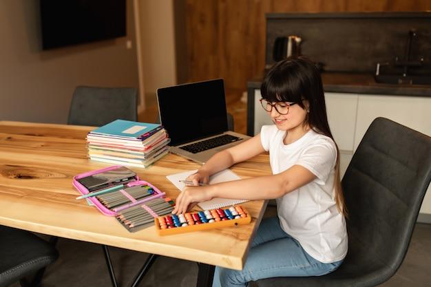 Online leren thuis. schoolmeisje met een laptop huiswerk. afstandsonderwijs tijdens quarantaine