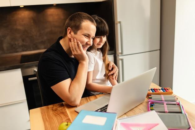 Online leren voor het hele gezin. schoolmeisje en haar vader thuis, online les, video-oproep op laptop. afstandsonderwijs, thuisschool. samenhorigheid in het gezin