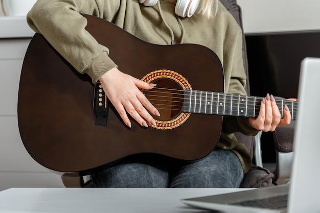 Online lessen cursus gitaartraining muziek e educatie tijdens lockdown. online muzikaal gitaarspel. jonge vrouw speelt akoestische gitaar thuis voor online publiek op laptop.