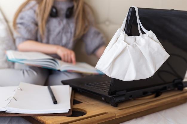 Online lessen voor schoolkinderen thuis. meisjeszitting met laptop en een boek in bed. coronavirus in quarantaine plaatsen