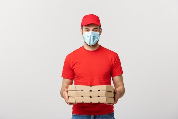 Online levering en coronavirus concept. vrolijke jonge bezorger in de pizzadozen van de gezichtsmaskerholding terwijl geïsoleerd op witte studiomuur