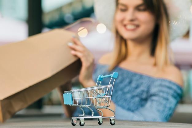 Online mini winkelwagentje close-up met onscherpe achtergrond van jonge shopaholic vrouw