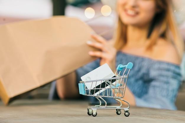 Online mini winkelwagentje met een bankkaart close-up met onscherpe achtergrond van jonge shopaholic vrouw