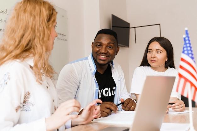 Online multi-etnisch aantrekkelijke groep leraren studeren en lachen, iets bespreken