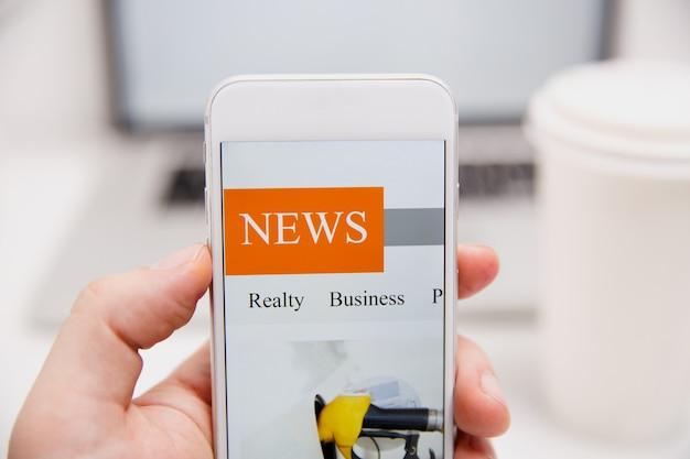 Online nieuws in mobiele telefoon. sluit omhoog van het smartphonescherm. man leest artikelen in toepassing. hand met slim apparaat. mockup-website. krant en portaal op internet