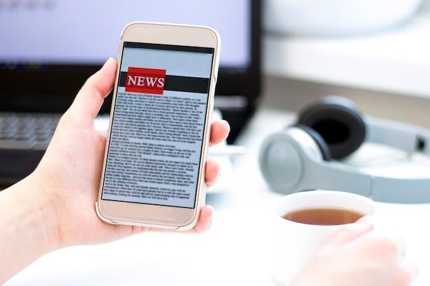 Online nieuws op een mobiele telefoon. sluit omhoog van het nieuws of de artikelen van de onderneemsterlezing in een toepassing van het smartphonescherm. hand met slim apparaat.