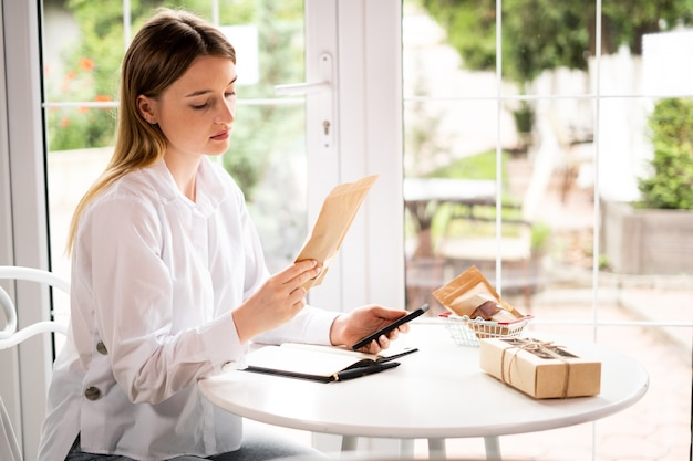 Online ondernemer blanke vrouwen dragen een wit overhemd, kijken naar smartphone, controleren de bestelling, veel dozen met pakketten met pakjes en kar op tafel in café bij raam. verkoopconcept
