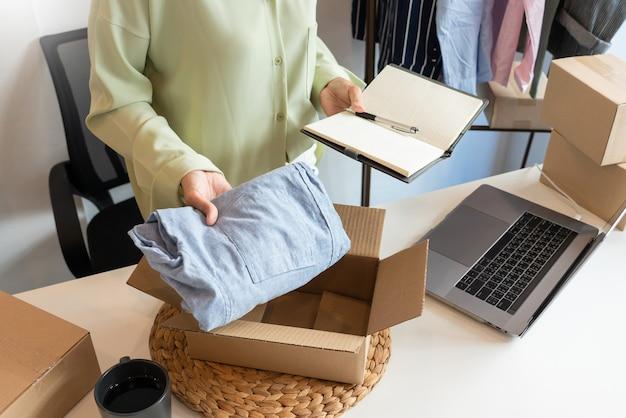 Online ondernemershandelaren voor kleine bedrijven die in de winkel werken die producten voorbereiden om aan klanten, opstarten en online bedrijfsconcept te leveren.