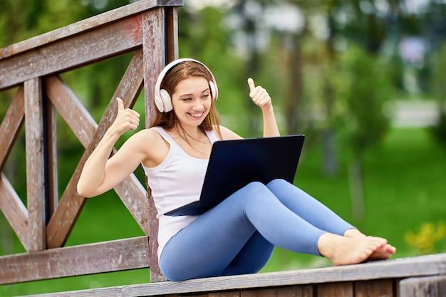 Online onderwijs door vrouw in draadloze koptelefoon buitenshuis