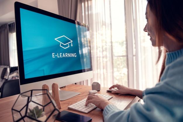Online onderwijs, e-learning. jonge vrouw zit aan tafel, werkt op computermonitor met inscriptie op scherm