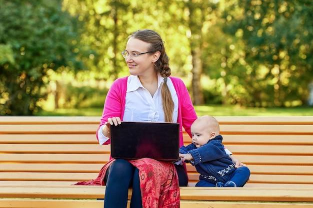 Online onderwijs met behulp van laptop door europese vrouw met baby op bankje in het park