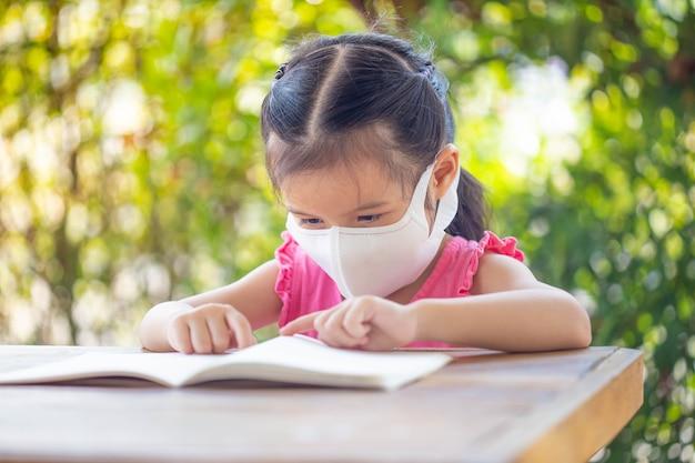 Online onderwijs op afstand. kind in een masker om een online les te kijken.