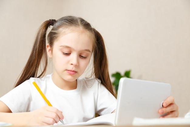 Online onderwijs op afstand. schoolmeisje thuis studeren met digitale tablet laptop notebook en school huiswerk.