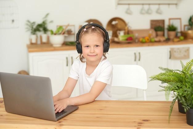 Online onderwijs voor kinderen. een schoolmeisje kijkt naar de camera terwijl ze thuis studeert met een laptop. quarantaine.