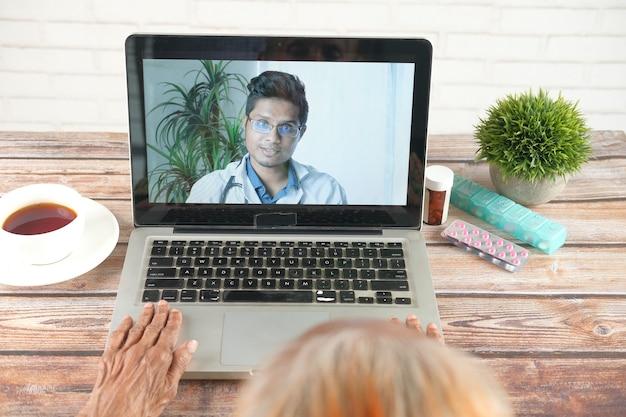 Online overleg met arts op laptop en met medische pillenhouder