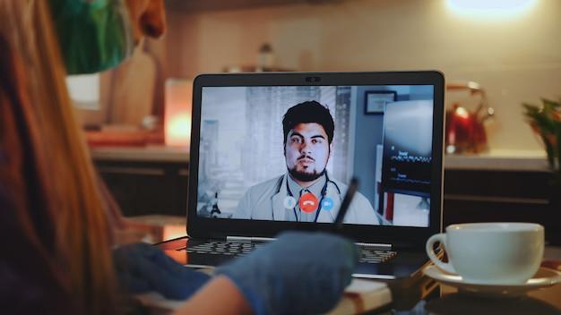 Online overleg met arts: vrouw in medisch masker en handschoenen die zijn adviezen schrijven
