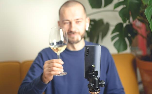 Online partij concept man met een glas witte wijn videobellen via smartphone