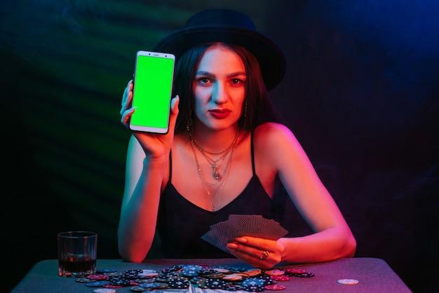 Online pokerspeler met een smartphone aan een casinotafel met kaarten en chips. de vrouw met de hoed is aan het gokken