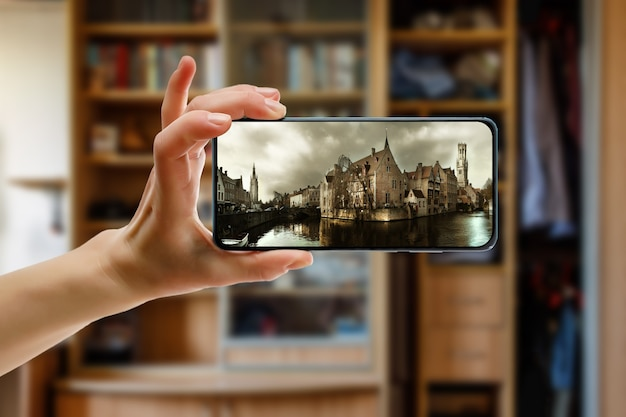 Online reis naar de europese oude stad brugge in belgië met een smartphone thuis.