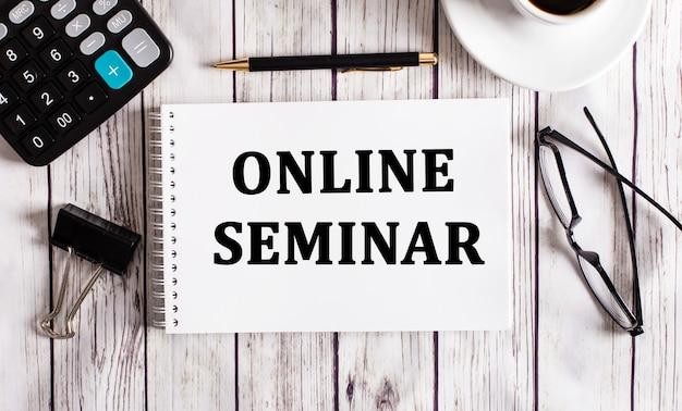 Online seminar is geschreven in een wit notitieblok naast een rekenmachine, koffie, glazen en een pen. bedrijfsconcept