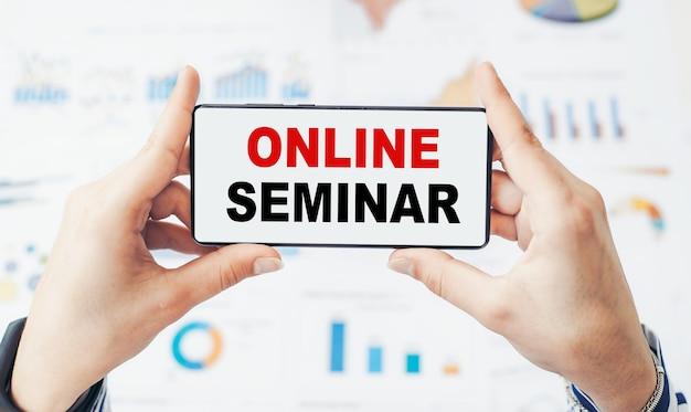 Online seminar - tekst op een smartphone in de handen van een vrouw over financiële grafieken