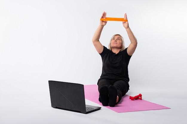 Online senior vrouw training met elastische band zittend op fitness mat