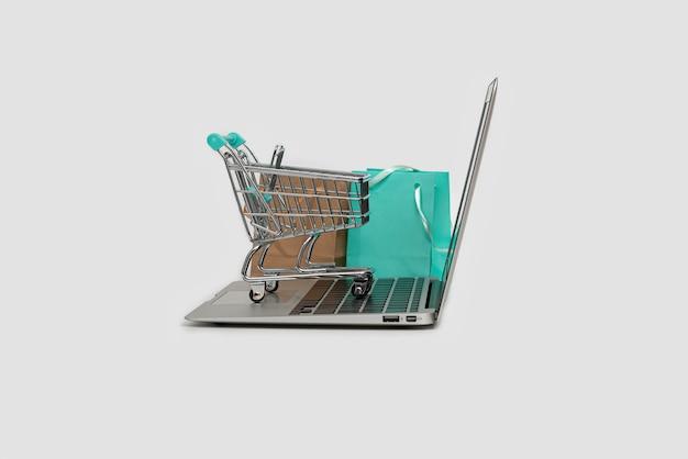 Online shopping concept met laptop, boodschappentas en trolley geïsoleerd op wit, kopieer ruimte