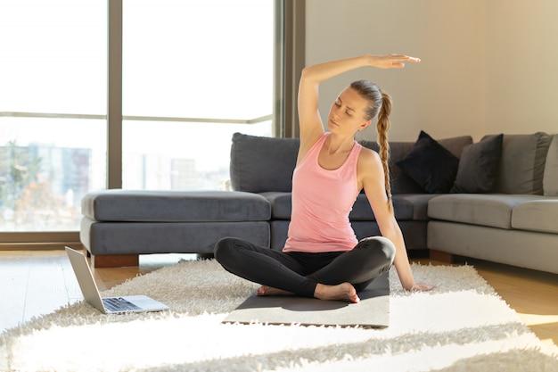 Online sport fitness yoga training. jonge vrouw en het doen van oefeningen op yogamat