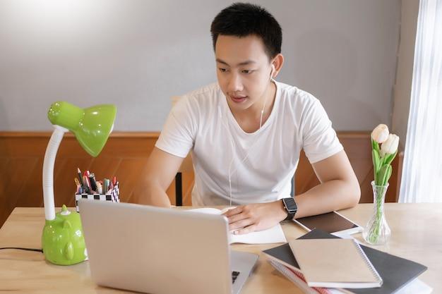 Online studieconcept de jonge man die wordt omringd door stapels boeken, bloemen en groene lamp die zich concentreert op het doen van zijn nieuwe project.