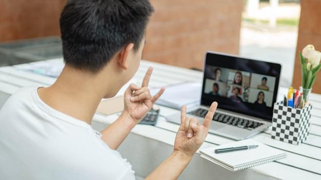 Online studieconcept de jonge universiteitsstudent die zijn klasgenoten voor het eerst ontmoet tijdens online lessen en ze begroet met een handteken door zijn wijsvinger en pink te tonen.