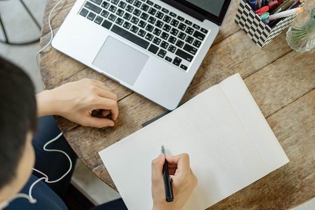 Online studieconcept een zwartharige student die zijn huiswerk doet door informatie op internet te zoeken en deze zwarte pen te gebruiken om de conclusie van zijn onderzoek op papier te schrijven.