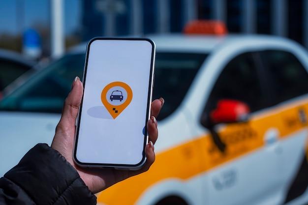 Online taxi in een smartphone. het meisje houdt de telefoon in haar handen met een mobiele applicatie op het scherm tegen de achtergrond van de auto.