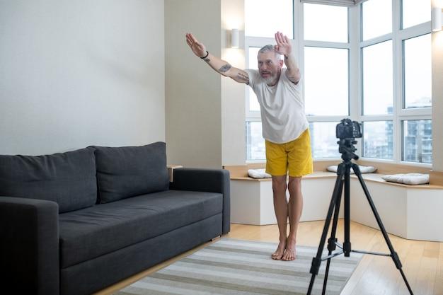 Online training. een volwassen man in een wit t-shirt die online yoga beoefent