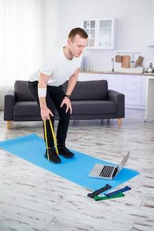 Online training. jonge man doet oefening met fitness elastiekjes met online tutorial thuis, vrije ruimte. thuis sporten