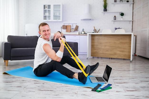 Online training. man doet oefening met elastiekjes thuis, vrije ruimte. thuis sporten