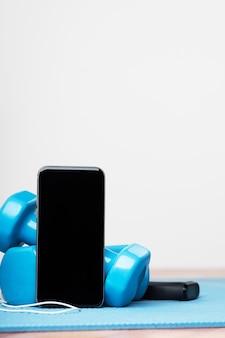 Online training. sport apparaten. trainen op muziek. halters, smartphone, oortelefoon en fitnessarmband. kopieer de ruimte op het display van de smartphone. isolatieperiode. thuis oefeningen concept.