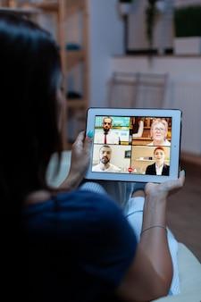 Online vergaderen met een tablet die thuis op een comfortabele bank ligt. externe werknemer die online vergadert met collega's over videoconferentie en webcamchat met behulp van internettechnologie.