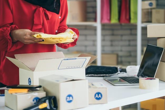 Online verkoper werkt thuiskantoor en verpakt verzenddoos aan klant.