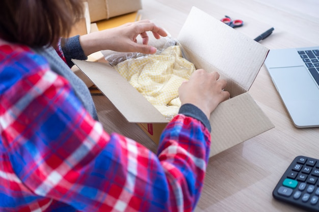 Online verkopers verpakken shirts in dozen om producten te leveren aan kopers die op de website bestellen